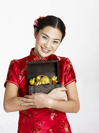chinese woman holding gold ingot Gold Gong Xi Fa Cai New Year Prosperity Red Treasure Beautiful Woman Cheongsam Chinese New Year Fortune Hair Bun Happiness Heritage Holding One Person Qipao Smiling Studio Shot White Background Young Adult Young Women