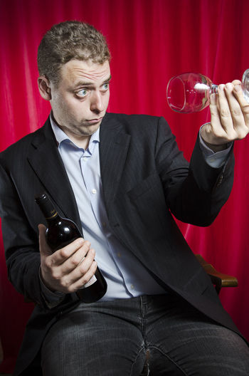 Drunk man with bottle looking in wineglass while sitting against red curtain