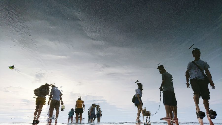 Reflection of people on wet beach