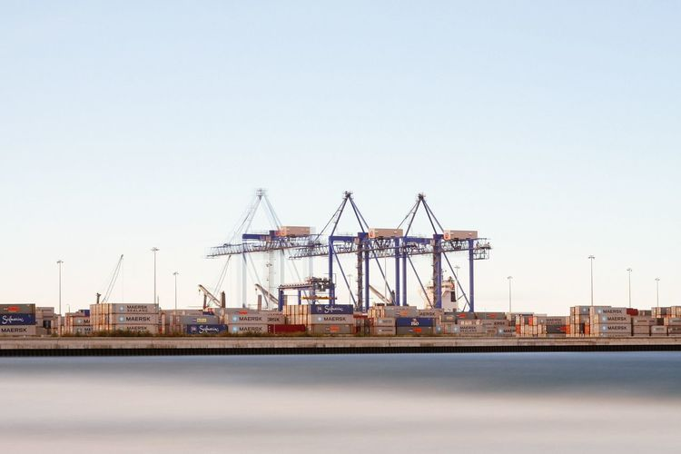 Cranes at commercial dock against clear sky