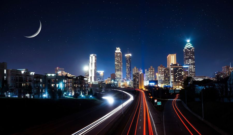Light trails on illuminated city against clear sky at night