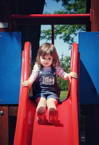Girl looking down while sitting on slide at playground