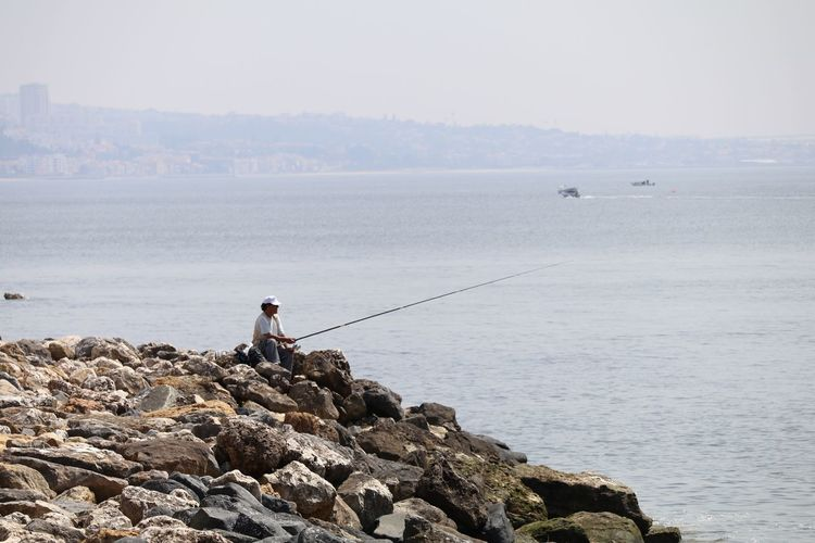 Man fishing by beach