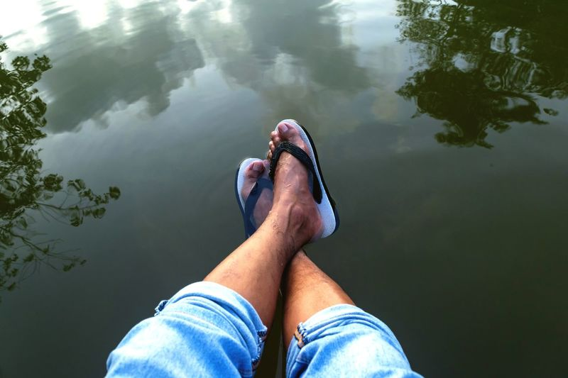 Low section of man relaxing over lake