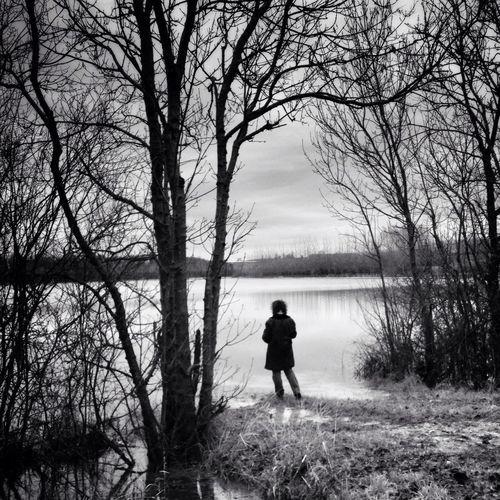 Woman standing at lakeshore