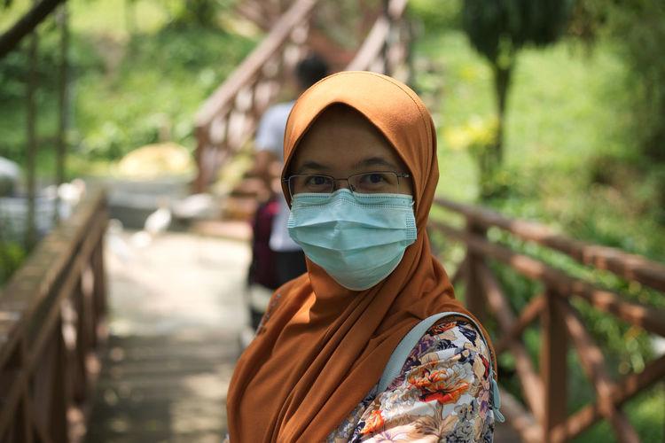 Portrait of woman wearing flu mask standing on footbridge in park