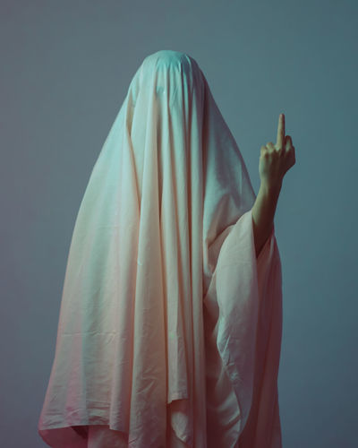 Person covered with fabric showing middle finger against gray background