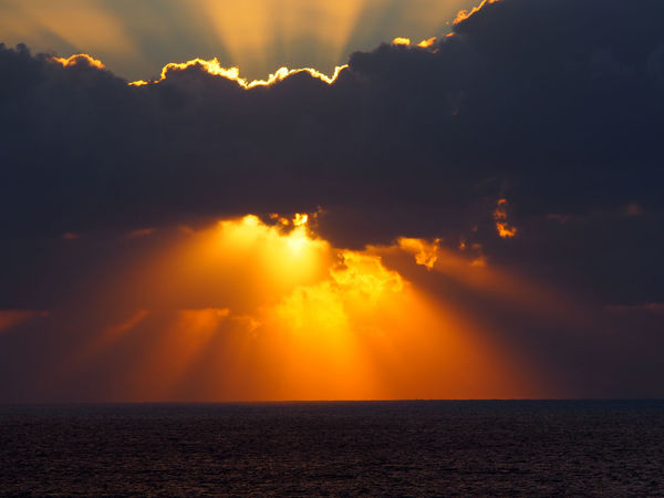 dramatic sunset over the sea with rays of light emerging from dark illuminated clouds over a calm ocean Sky Cloud - Sky Scenics - Nature Water Horizon Over Water Beauty In Nature Sunset Sea Horizon Tranquility Tranquil Scene Orange Color Nature No People Idyllic Sunbeam Sunlight Sun Waterfront Outdoors