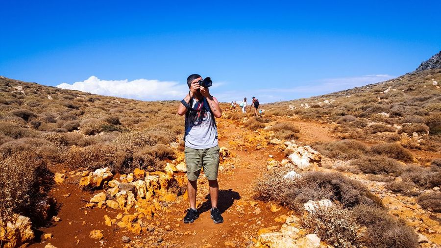 Man clicking photograph with camera on field against sky