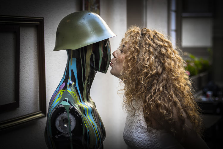 Side view of woman kissing mannequin