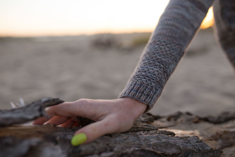 Cropped Hand Of Woman On Rock During Sunset