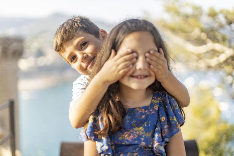 Portrait of brother blindfolding sister