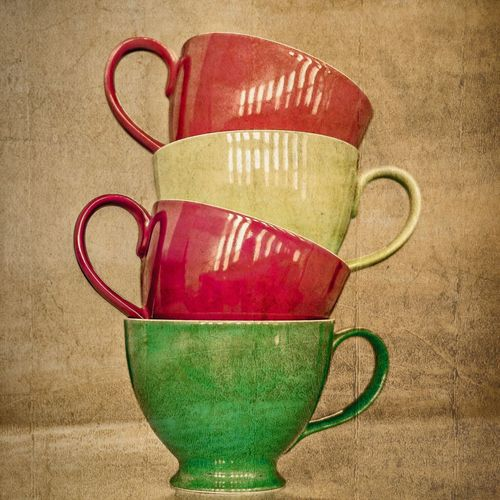 Close-up of stacked colorful tea cups by brown paper