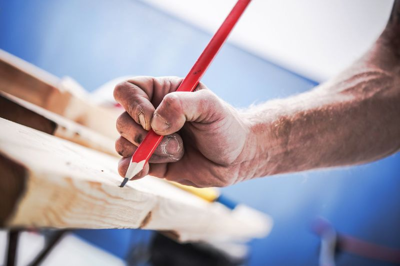 Passionate Carpenter at Work. Woodwork Concept. Carpenters Hand with Pencil Marking the Cut. Adult Carpenter Close-up Craftsperson Day Holding Human Body Part Human Hand Indoors  Manual Worker Men Occupation One Person People Real People Skill  Wood - Material Work Tool Workbench Working Workshop
