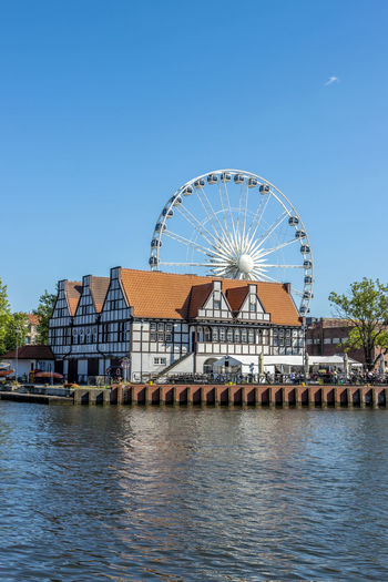 Ferris wheel by river against buildings against clear blue sky