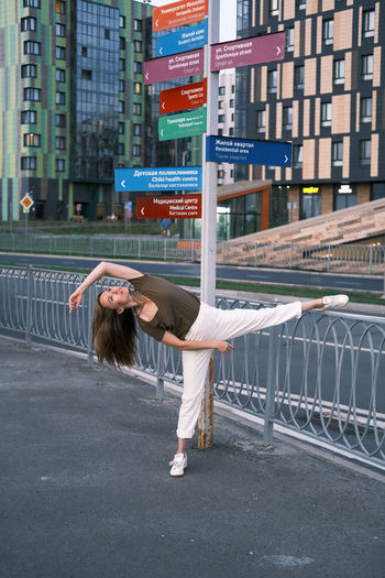 Pretty woman dressed in white pants and olive t-shirt dancing and stretching in the street.