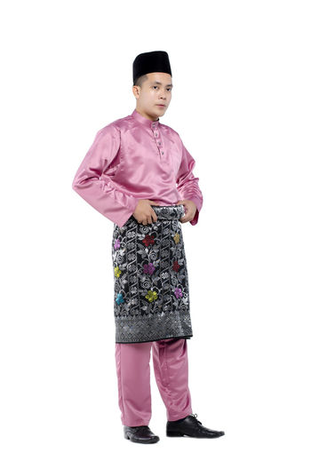 Portrait of young and handsome asian man with traditional clothing during hari raya over white background Studio Shot White Background One Person Indoors  Standing Cut Out Front View Pink Color Copy Space Full Length Clothing Looking At Camera Child Childhood Traditional Clothing Females Portrait Casual Clothing Purple Isolated