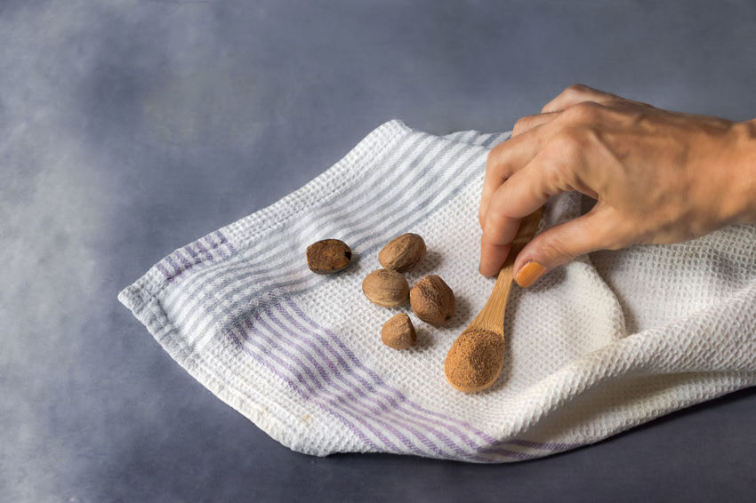 Nutmeg grain and ground on a kitchen towel, on a dark wood background Adult Aroma, Scent, Texture Aromatic Herbs Childhood Close-up Colored Background Condiment Dish Towel Food Food And Drink Hand Healthcare And Medicine Healthy Lifestyle Holding Human Body Part Human Hand Indoors  Ingredient Napkin Nocooking Nut Nutmeg, Spice, Seed One Person Studio Shot Textile