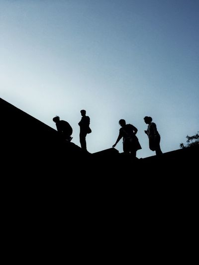 Low angle view of silhouette men against clear sky