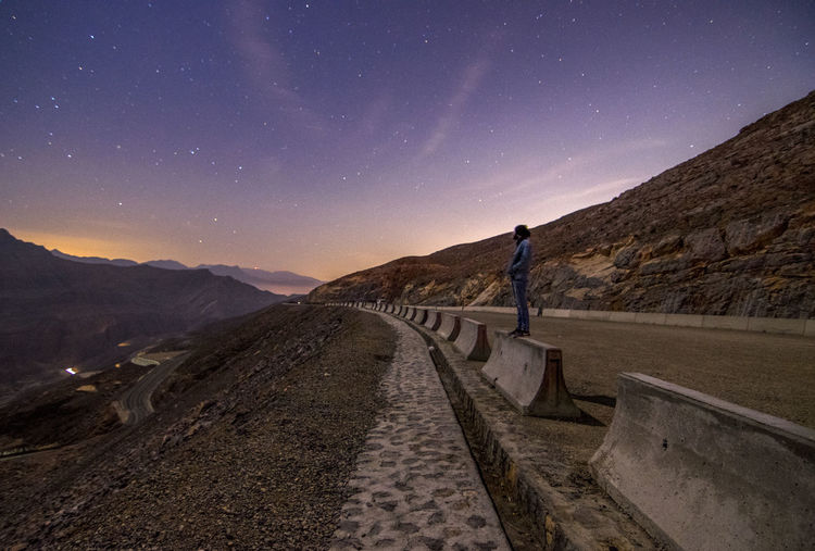 Side view of man standing on road at night