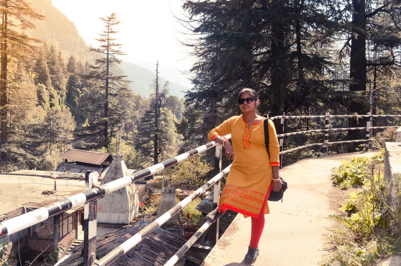 A woman standing in the heart of Manali City, Himachal Pradesh, Kullu, is a popular tourist destination in northern India. Himalaya, Himalayan-valley, Summer, Tranquil Bridge, Mountain, Forest, Scenic, Beautiful, Peaceful Clothing Daybreak, Standing-looking, Relaxation Daytime, Female, Asia, Smart, Hilly, Hills, Mountains Destination, Tourism, Indian, Asian, Fashionable Fall-autumn, Countryside, Beauty, Outdoors, Fashion Full Length Hill Station, Young, Travel, Girl-lady, Himalayas, Winter-vacation, Sensuality, Casual-dress, Serene, Sporty, Background, Leisure Activity Lifestyles Nature One Person Outdoor, Person, Scenery-scene, Portrait, Teenager, Stylish, Outdoors Railing Real People Standing Transportation Travel Tree Young Adult Youngster, Model, Northern, Offbeat International Women's Day 2019