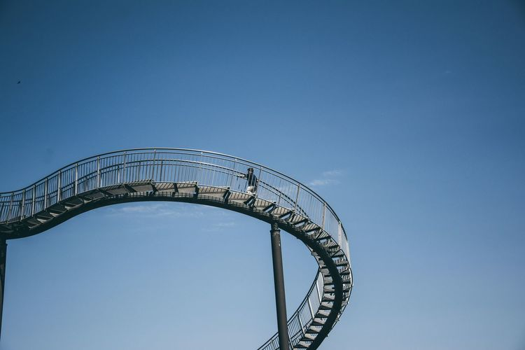Low Angle View Of Man On Rollercoaster Against Blue Sky