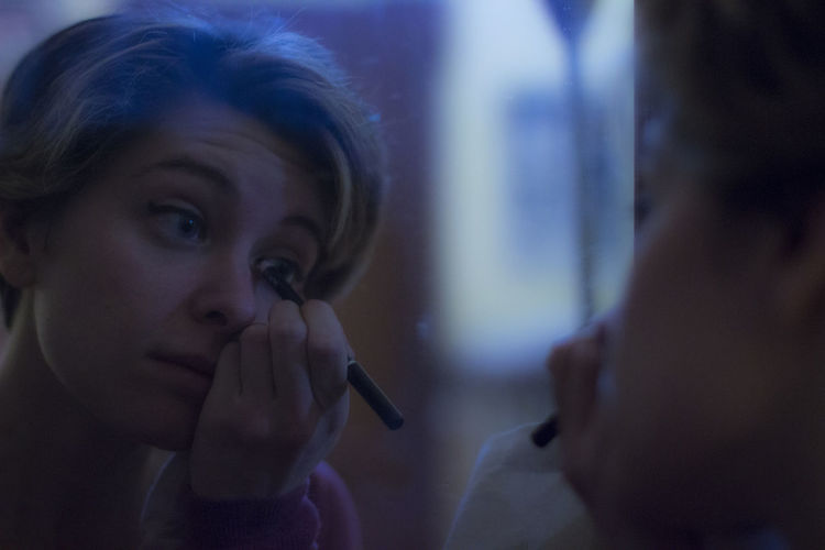 Reflection Of Young Woman Applying Mascara On Mirror
