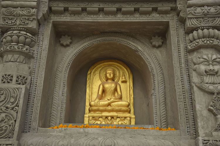 Golden Buddha statue in Buddhist art. Bas Relief Carving - Craft Product Architecture Arch History Travel Destinations Built Structure