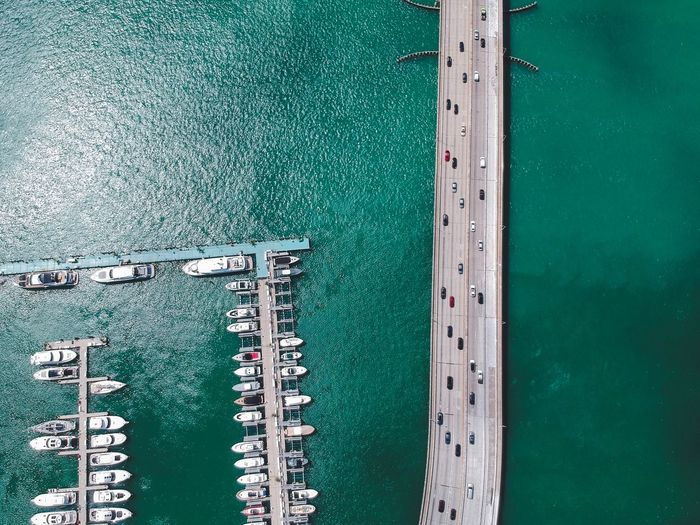 Aerial view of boats moored on sea by bridge