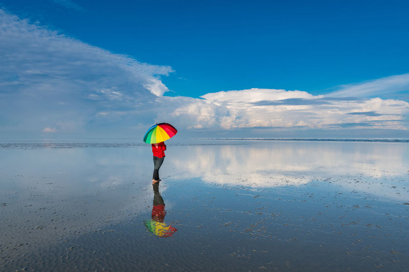 Rear view of woman with umbrella standing at beach against cloudy sky