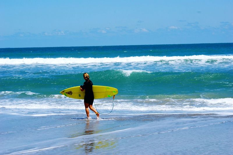 Rear View Of Female Surfer Carrying Surfboard On Shore