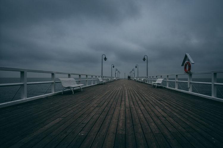 Pier on bridge in city against sky