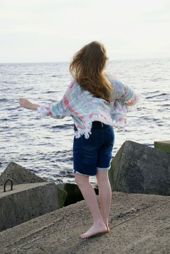 Woman dancing on pier by sea against sky