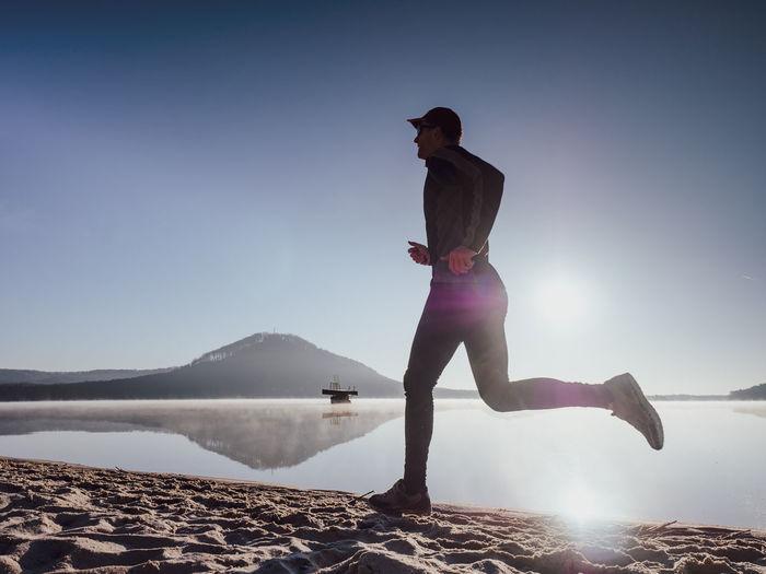 Full length of man standing in lake against sky