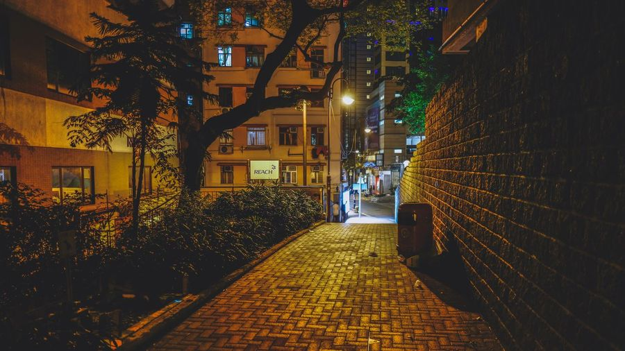 Illuminated footpath amidst buildings at night