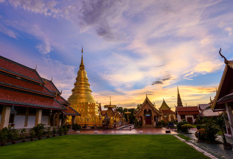 Wat Phra That Hariphunchai with Twilight time in Lamphun Province, Thailand. Most famous temple in northern of Thailand. Ancient Buddha Gold Lamphun Pagoda Thailand Wat Phra That Hariphunchai Architecture Belief Buddhism Built Structure Cloud - Sky Culture Destination, Evening, History Religion Sky Temple Tourism Tower Traditional Twilight, Sky,dusk,