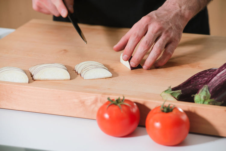 Midsection Of Man Cutting Eggplant On Kitchen Island