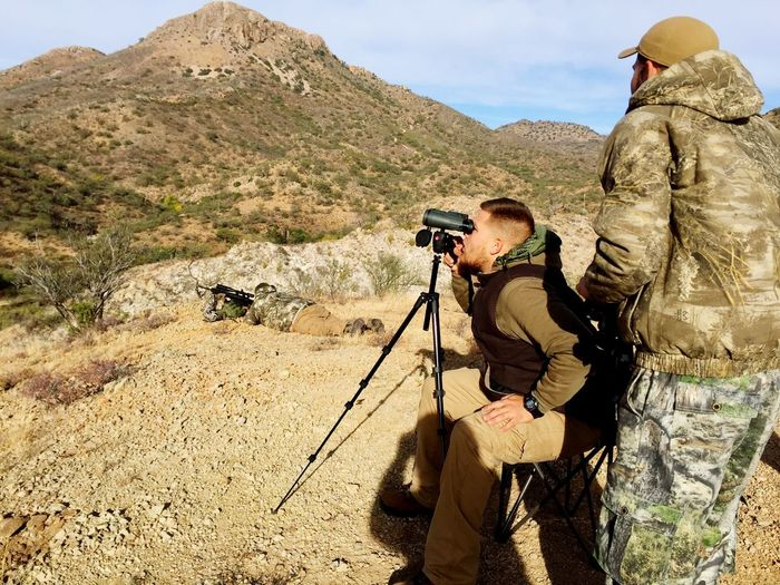 Side View Of Soldier Using Binoculars On Mountain Against Sky