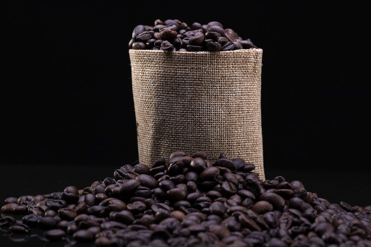 A coffee beans over the black background Food And Drink Large Group Of Objects Roasted Coffee Bean Freshness Still Life Food Abundance Indoors  Coffee Coffee - Drink Sack Black Background Close-up Container No People Studio Shot Brown Raw Food Healthy Eating Heap Caffeine