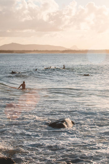 People swimming in sea against sky during sunset