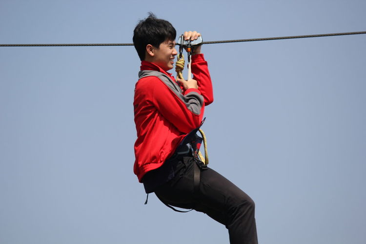 Activity Boys Clear Sky Copy Space Day Holding Leisure Activity Lifestyles Low Angle View Males  Men Nature One Person Real People Red Side View Sky Sport Three Quarter Length