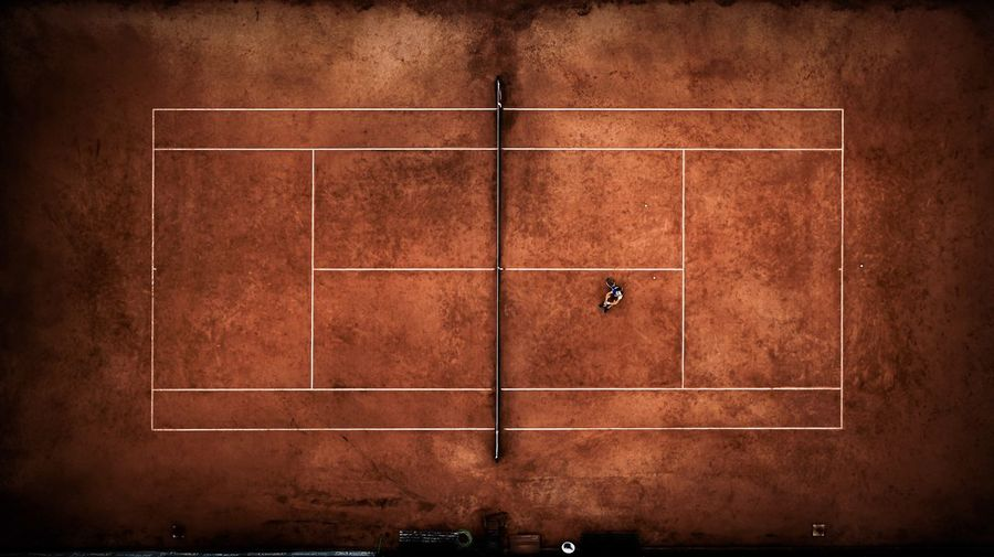 Aerial view of man sitting at tennis court