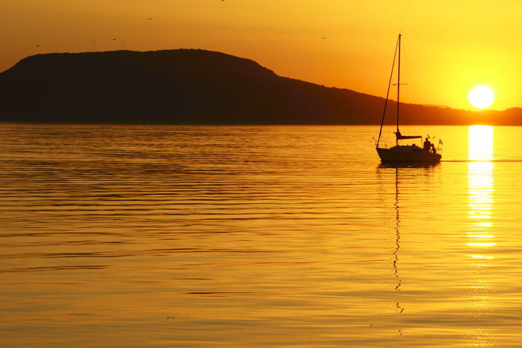 Orange Sky Beauty In Nature Mast Mode Of Transport Moored Mountain Nature No People Orange Color Outdoors Reflection Sailer Sailing Scenics Silhouette Sky Sunset Tranquil Scene Tranquility Transportation Water Waterfront