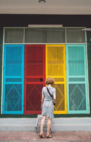 Full length of woman walking against multi colored doors