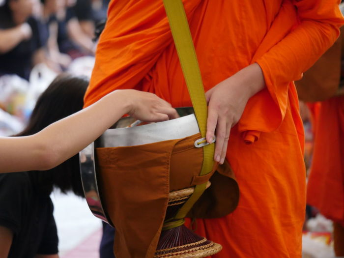 Midsection Of Monk Serving Food