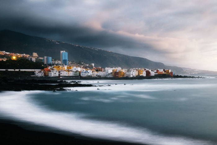 View of colorful houses of Puerto de la cruz, Jardin beach with black sand and Atlantic ocean, Tenerife, Canary islands, Spain. Long exposure Atlantic Ocean Canary Islands Cloudscape Puerto De La Cruz Seascape Photography Built Structure Cityscape Cloud - Sky Cloudsporn Long Exposure Longexposure No People Sea Sky Tenerife Water Waterfront