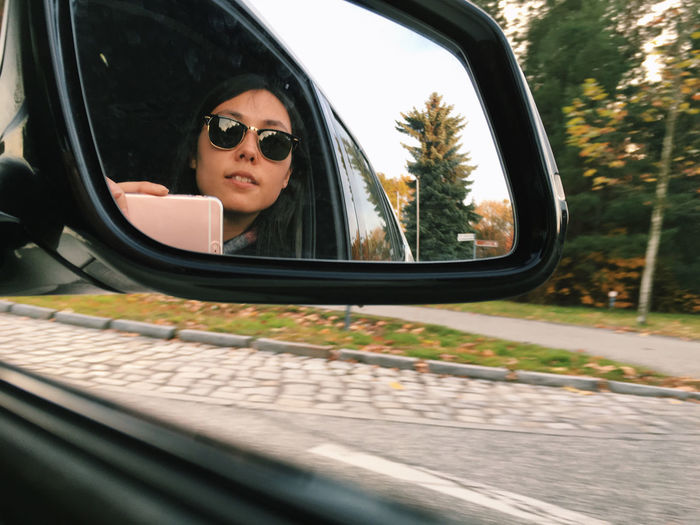 Young Woman Seen In Rear-View Mirror While Sitting In Car