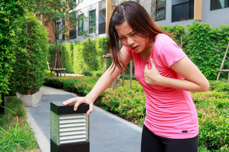 Woman suffering from chest pain while standing on footpath
