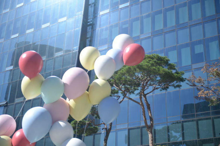 Architecture Balloon Building Building Exterior Built Structure Celebration City Day Decoration Glass - Material Helium Balloon Low Angle View Multi Colored Nature No People Office Building Exterior Outdoors Red Sky Skyscraper Sunlight