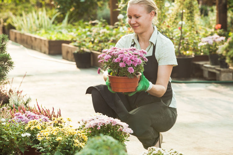 Beautiful young woman sitting on flower pot